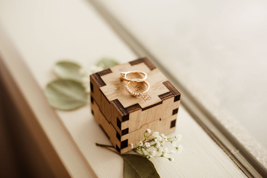 wedding ring box with rings on top and greenery.